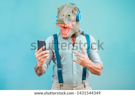 Crazy tattooed man with t-rex mask using smartphone while listening music - Crazy senior male having fun with mobile phone app - Technology trends and fashion concept - Focus on face #1431544349