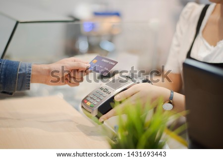 Hand of man customer using wireless or contactless payment of a credit card. Young Asian cashier or seller are smiling to accept payment by nfc technology at retail shop. Contactless payment concept. #1431693443
