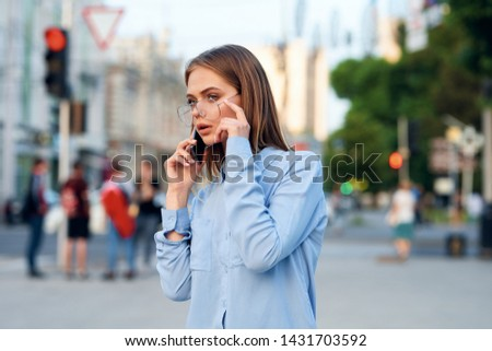 woman with phone walks through the city street #1431703592