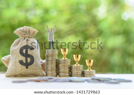 Business tycoon, career success concept : Miniature figurine businessman raises his hands, US dollar bags, golden trophy cups on rows of increasing coins, depicts the ambition obtain intended results #1431729863