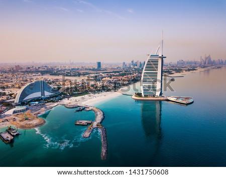 Burj Al Arab luxury hotel and Dubai marina skyline in the background at sunrise Royalty-Free Stock Photo #1431750608
