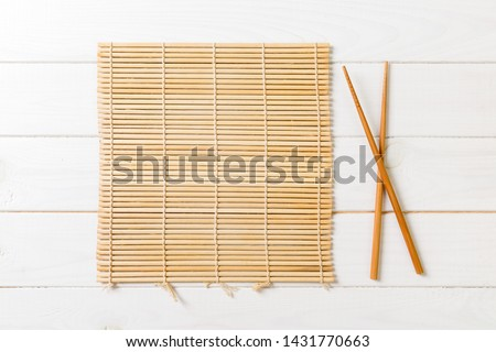 two sushi chopsticks with empty bamboo mat or wood plate on wooden Background Top view with copy stace. #1431770663
