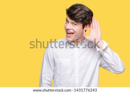 Young handsome business man over isolated background smiling with hand over ear listening an hearing to rumor or gossip. Deafness concept. #1431776243
