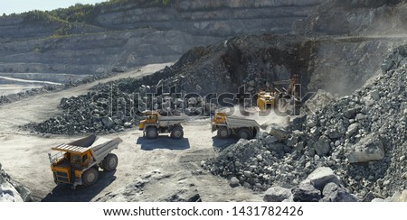 Excavator and heavy mining dump trucks in a limestone quarry, loading of stone ore, industrial panorama. Royalty-Free Stock Photo #1431782426