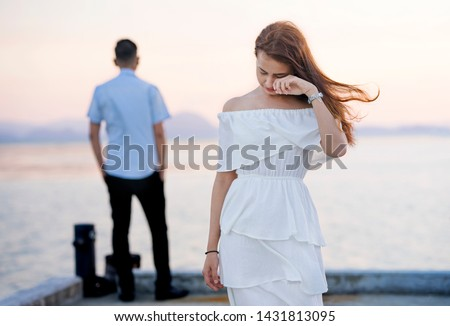 Young couple break up at the sea deck. Girl crying and walk away from man in concept love hurts,hard relationship,sad love story,when love is ended. Broken heart syndrome. How to fix a broken heart. #1431813095