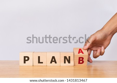 Hand flip wooden cube with the word PLAN A to PLAN B on white background. Business concept Royalty-Free Stock Photo #1431813467