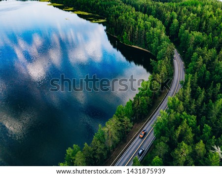 Aerial view of road between green summer forest and blue lake in Finland #1431875939