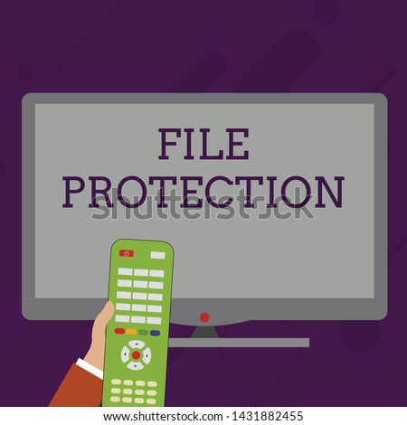 Word writing text File Protection. Business concept for Preventing accidental erasing of data using storage medium Hand Holding Computer Remote Control infront of Blank Wide Color PC Screen.