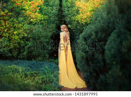 Slender beauty in elegant bright dress with stretching trains goes to thick of magical garden, golden elf princess with bare trimmed seductive back golden long light braided hair looks at her plants. #1431897995