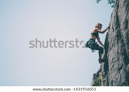 Climber overcomes challenging climbing route. A girl climbs a rock. Woman engaged in extreme sport. Extreme hobby. #1431956051