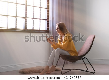 Young woman using smartphone near window with blinds at home. Space for text #1431962552