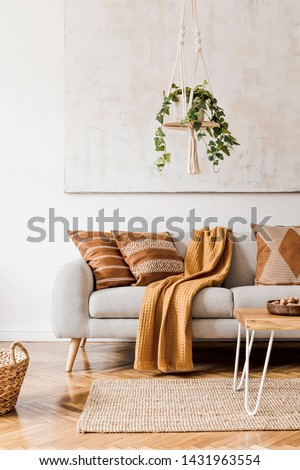 Modern boho interior of living room at cozy apartment with gray sofa, honey yellow pillows and plaid, plants, paintings, rattan basket and design personal accessories. Stylish home decor. Template. #1431963554