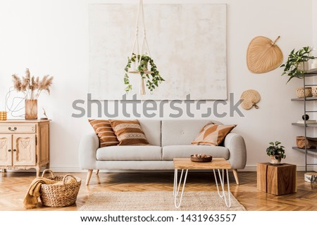 The stylish boho compostion at living room interior with design gray sofa, wooden coffee table, commode and elegant personal accessories. Honey yellow pillow and plaid. Cozy apartment. Home decor #1431963557
