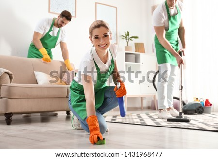 Woman using sponge and detergent for floor cleaning with her team in living room #1431968477