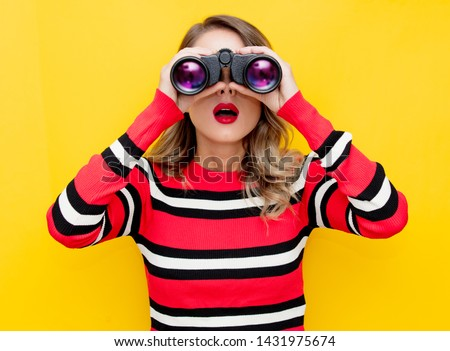young woman in striped sweater with binocular on yellow background  Royalty-Free Stock Photo #1431975674
