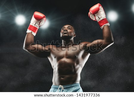 Champion. African boxer raising his arms in winner gesture, stadium lights background Royalty-Free Stock Photo #1431977336