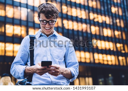 Happy smiling male entrepreneur reading positive sms text while chatting via cellphone app, cheerful employee in optical spectacles for vision correction laughing while receiving funny content #1431993107