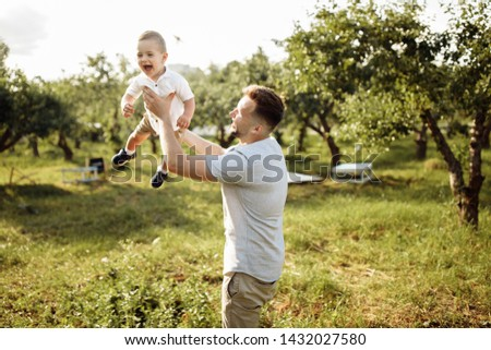 Happy young father with little son play in the park at summer  #1432027580