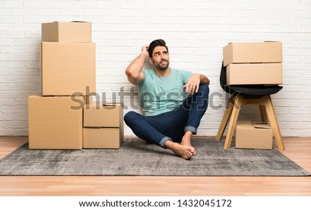Handsome young man moving in new home among boxes having doubts and with confuse face expression