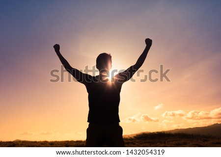 Strong young man with fist in the air standing on top a mountain. Triumph, victory and feeling determined. Royalty-Free Stock Photo #1432054319