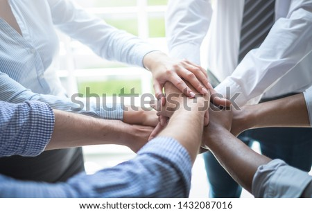 Close up view of young business people putting their hands together. Stack of hands. Unity and teamwork concept. #1432087016