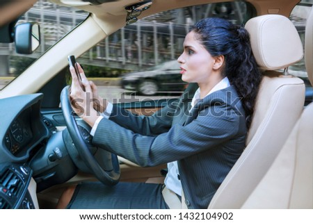 Young businesswoman driving a car while using a mobile phone on the road #1432104902