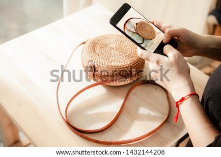Women taking photo to Bags and products with cell telephone or smartphone digital camera for Post to sell Online on the Internet .