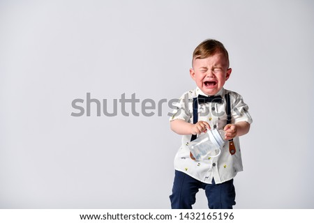 Crying baby. Portrait of a kid in full growth in the studio on a white background. Dressed in a suit of a gentleman - white shirt and pants with straps. Baby Emotions #1432165196