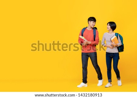 Asian girl and boy students with bags holding books in a conversation while walking towards class college isolated against yellow studio background #1432180913