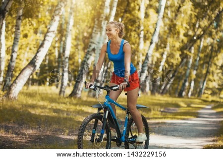 cute blonde woman cyclist cycling mountain bike on the birch forest trail #1432229156