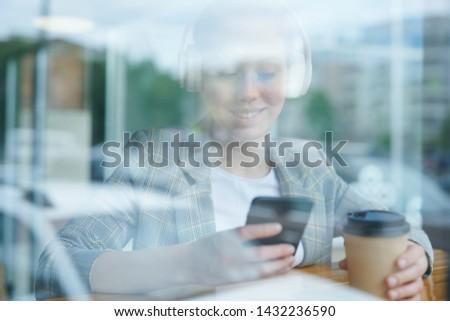 Modern girl choosing audio on gadget #1432236590