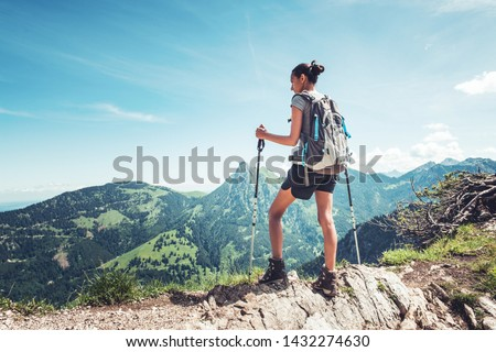 Fit young woman hiking in the mountains standing on a rocky summit ridge with backpack and pole looking out over an alpine landscape #1432274630