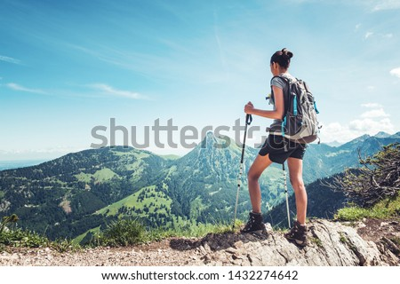 Fit female hiker with backpack and poles standing on a rocky mountain ridge looking out of green alpine valleys and peaks in a healthy outdoors lifestyle concept #1432274642