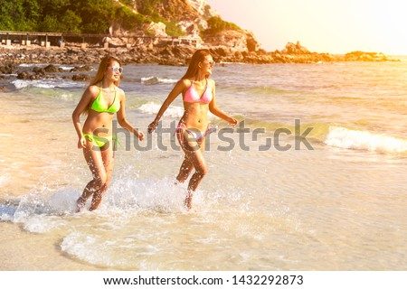 Couple girl running on the beach relaxing summer vacation.Young fashion woman relax on the beach. Happy island lifestyle.crystal. Vacation at Paradise. Ocean beach relax. Royalty-Free Stock Photo #1432292873