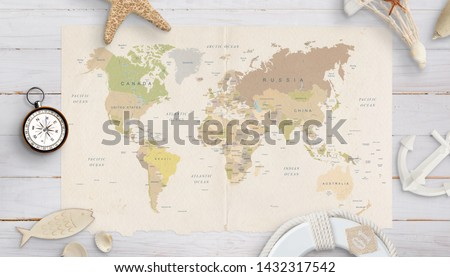 World map on a table surrounded by shells, compass, anchor and lifebelt. The concept of holiday planning in distant countries. Royalty-Free Stock Photo #1432317542