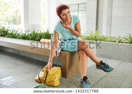 Young woman talking on phone when searching something in her bag #1432317788
