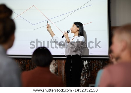 Side view portrait of contemporary businesswoman giving presentation pointing at graph lines on projector screen during lecture, copy space #1432332158