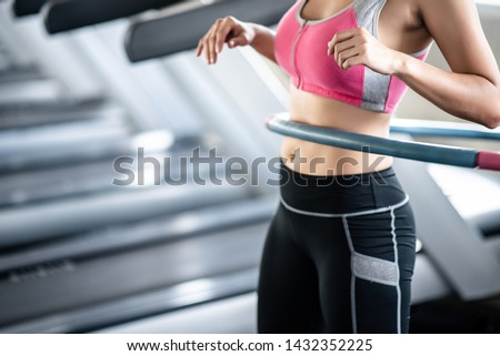 Young woman ratating hoola hoop in the gym Royalty-Free Stock Photo #1432352225