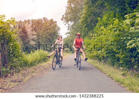happy couple biking on a summer sunny day in a beautiful nature - healthy lifestyle, leisure activity, holiday, relationship concept #1432388225