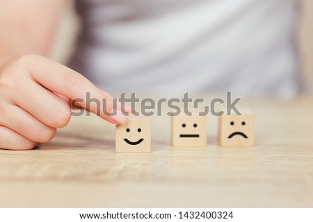 customer pressing smiley face emoticon on wood cube, Service rating, satisfaction concept. #1432400324