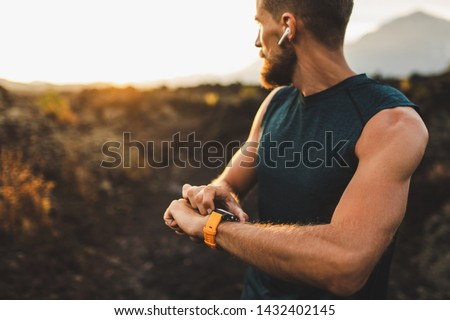 Athletic runner start training on fitness tracker or smart watch and looking forward on horizon. Trail running and active lifestyle concept. Royalty-Free Stock Photo #1432402145