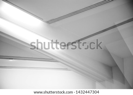 Ceiling and glowing girders. Abstract architecture fragment. Modern office building interior with polygonal white concrete elements. Diagonal geometric composition in light gray halftones.