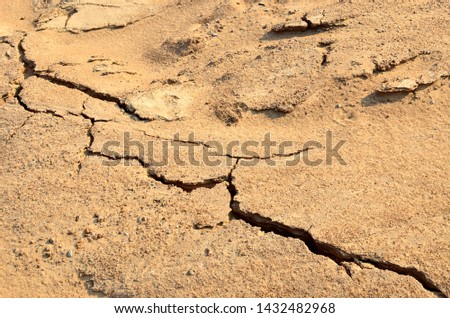 Dry lake or swamp in the process of drought and lack of rain or moisture, a global natural disaster. The cracked soil of the earth due to climate change. Background or texture of sand in mining quarry #1432482968
