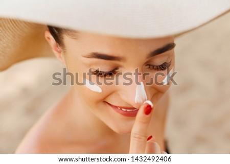 Suntan lotion woman applying sunscreen solar cream. Beautiful happy cute woman  applying suntan cream to her nose. #1432492406