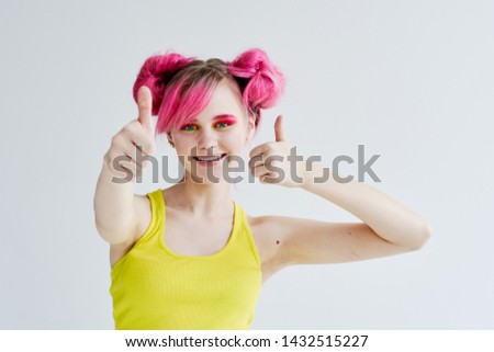 smiling woman with pink hair shows thumbs up on a light background ok signs #1432515227