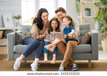 Happy loving family. Young mother, father and their daughters girls playing at home. Funny mom, dad and lovely children are having fun with tablet. #1432552025