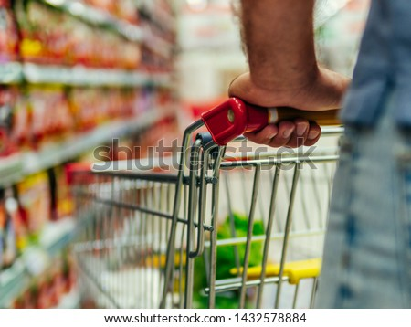 Shopping cart in supermarket. Caucasian or latin man hands hold shopping trolley in supermarket aisle. #1432578884