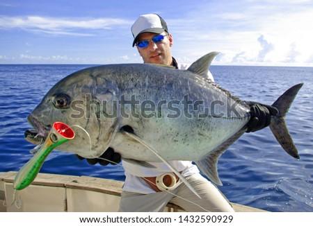 Deep sea fishing.  Catch of fish. Big game fishing, boat fishing, lure fishing, Fisherman holding a big Trevally jack  #1432590929