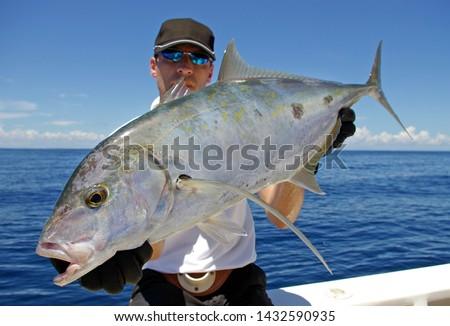 Deep sea fishing.  Catch of fish. Big game fishing, boat fishing, lure fishing, Fisherman holding a big Trevally jack  #1432590935