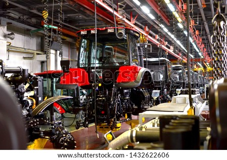 Tractor Manufacture work. Assembly line inside the agricultural machinery factory. Installation of parts on the tractor body - Image #1432622606